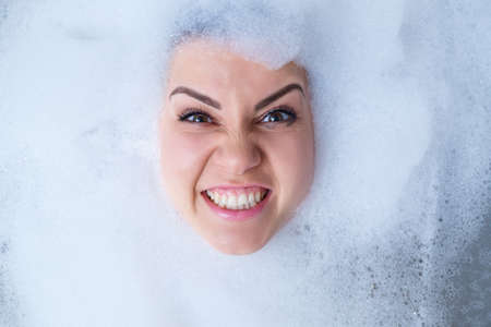 Closeup portrait of a girl in a bathtub and white foam around her face. Different emotions, grimaces, woman smile