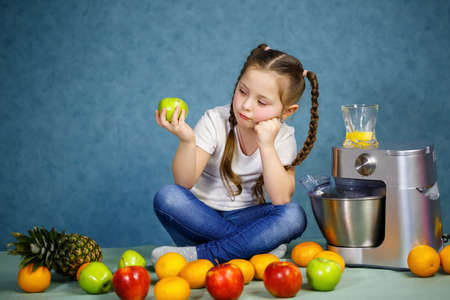 Little girl squeezed fresh juice from fruits of apples and orange. Vitamins and healthy nutrition for children. Stockfoto