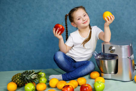 Little girl squeezed fresh juice from fruits of apples and orange. Vitamins and healthy nutrition for children.