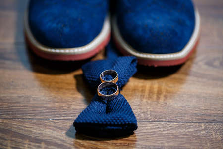 Gold wedding rings of the newlyweds lie next to men's shoes for the groom