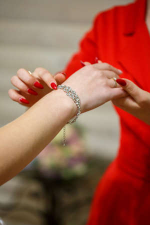 bride puts on wedding jewelry on the wedding day