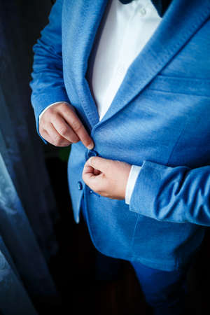 man puts on a suit on the wedding day