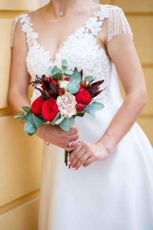 Beautiful wedding bouquet of flowers in the hands of the newlyweds