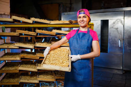 Make the noodles. Pasta factory. Spaghetti production. Raw pasta. Worker with a box of pasta. Girl works in the production of pasta