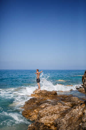 A young man stands on the rocks overlooking the open Mediterranean Sea. A guy on a warm summer sunny day looks at the sea breeze Imagens