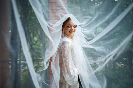 beautiful bride in a wedding morning in a bathrobe and veil