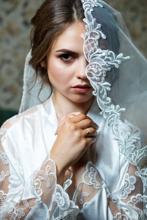 Photo close-up portrait of a bride with professional makeup, she is in a white coat, veil on her face. Young woman wedding day. Photoshoot, hairstyle, beauty