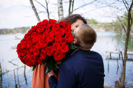 Romantic meeting of young people. A young woman agreed to marry her man. A guy in a suit with a bouquet of red roses gives the girl a bouquet, and they kiss in the forest