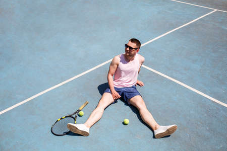 Handsome man in a T-shirt and shorts sits on a tennis field with a racket. Guy in sunglasses