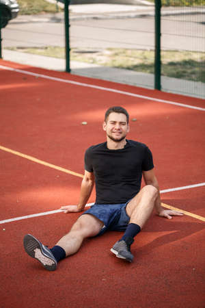 A young male athlete with a beard sits on a red tennis court. Handsome guy in t-shirt and shorts