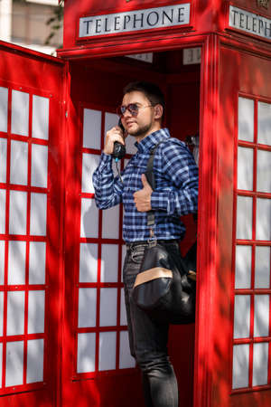 A handsome male businessman with a beard and a bag is standing in a red telephone booth and talking. Handsome guy in shirt and glasses with phone