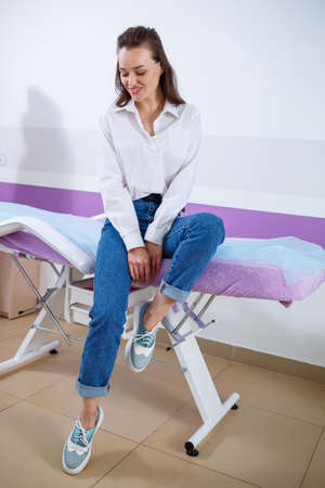 Beautiful young girl, a patient at a doctor's appointment at the medical center, dressed in jeans and a white shirt