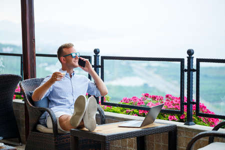male businessman working on a laptop on vacation with a beautiful panoramic view. Successful manager drinking coffee and talking on the phone with coffee while traveling Imagens
