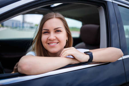 Elegant blonde beautiful woman sitting in a luxury car. The girl is stylish and earns a lot. independent woman businessman concept