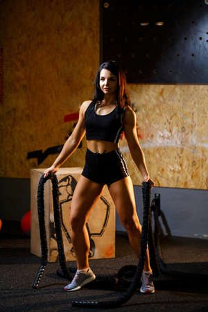 The girl in the gym with ropes in her hands