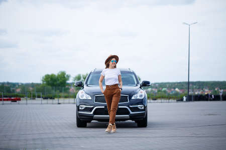 A beautiful girl of European appearance with glasses and a brown hat is standing near a black car.