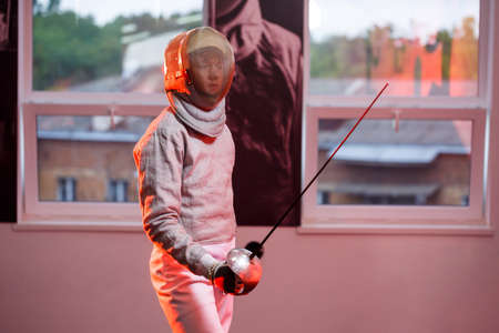 A guy in a fencing suit with a sword in his hand, neon light. A young model trains and trains in movement, action. Sports, youth, healthy lifestyle.