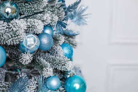 Beautiful Christmas tree in the winter interior of a photo studio, bedroom, New Year decoration. Blue balls Christmas toys. New Year is soon