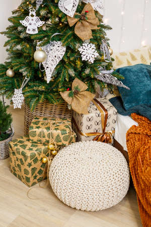 A cozy room decorated with garlands and Christmas trees. White pillow-bed is stylish and modern. Good New Year spirit. Light colors background texture place for text. Bedroom decor for the holiday