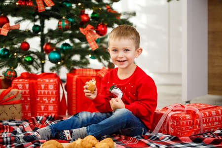 The boy who sits near the Christmas tree for the new year. Christmas decor with gifts, a child near the Christmas tree eats croissants and smiles