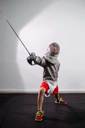 A child in a fencing costume is holding an epee. Girl learning fencing Banque d'images