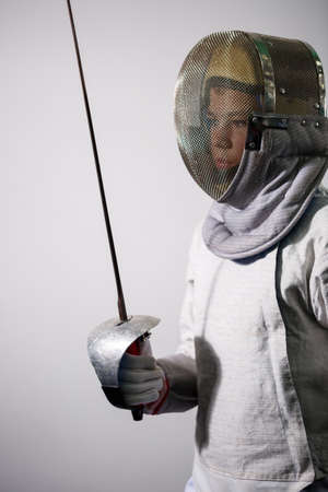 A girl in a fencing suit with a sword in hand. Young female model practicing and exercising. Sports, healthy lifestyle.