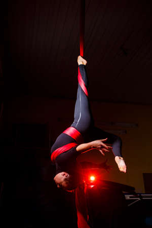 Portrait of a beautiful acrobat on canvas against a dark background. She does twine. Aerial gymnast