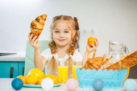 A little girl of seven, wearing a white T-shirt, sits at the kitchen table. Holds ripe mandarine and a freshly baked croissant with chocolate