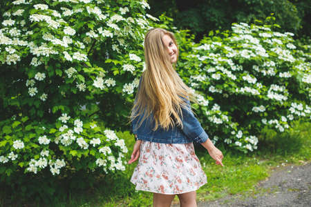 A young woman of European appearance with long blond hair, dressed in a short dress, stands against the background of white flowering bushes. Sunny spring day. Natural female beauty 写真素材