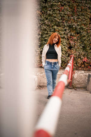 A pretty redhead young woman is walking down the street, she is dressed in jeans and a beige shirt. Beautiful girl dressed in casual style with a smile on her face