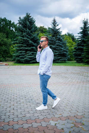 A handsome young man of European appearance wearing sunglasses is dressed in a shirt and jeans. The guy walks down the street, he is stylishly dressed