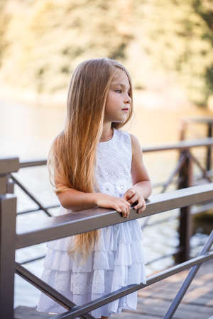 Portrait of a little girl outdoors in the summer by the lake. Little girl in summer dress by the river.