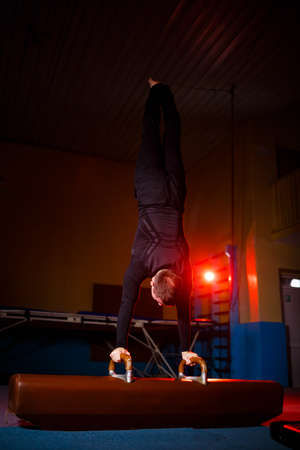 Adult man in sportswear doing exercises on gymnastic apparatus in the acrobatic gym
