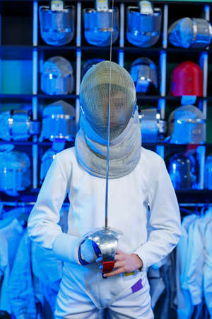Young guy in a fencing suit with a sword in his hand, on a blue background, neon light. The athlete trains. Sports, youth, healthy lifestyle.