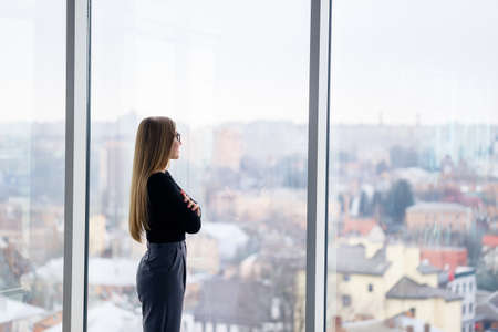 A successful female manager in her own office with large windows is standing and looking at the city. Business woman with glasses on the background of large windows