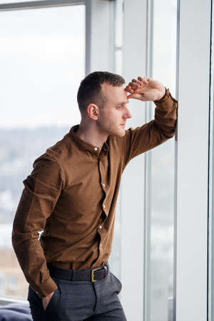A young successful male businessman stands loosely near a large window and looks out over the city.