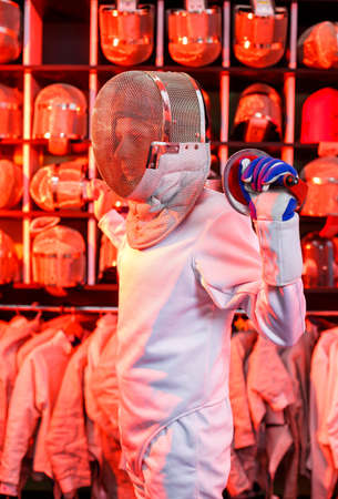 Young guy in a fencing suit with a sword in his hand, on a red background, neon light. The athlete trains. Sports, youth, healthy lifestyle. Selective focus
