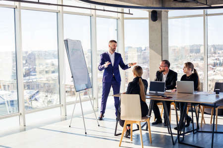Confident businessman makes a presentation of a new project in the boardroom at a company meeting. Beautiful auditors talk with different partners about the business using a whiteboard and graphs.