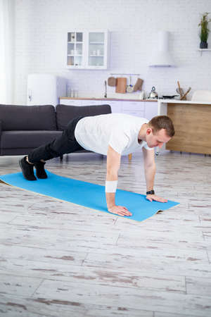 Handsome muscular man in a t-shirt doing functional plank exercises on the floor at home. Fitness at home. Healthy lifestyle.