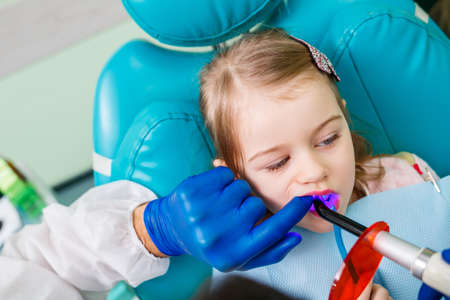 A professional doctor, a children's dentist, treats a little girl's teeth with instruments. Dental office for patient examination. The process of dental treatment in a child Stock Photo