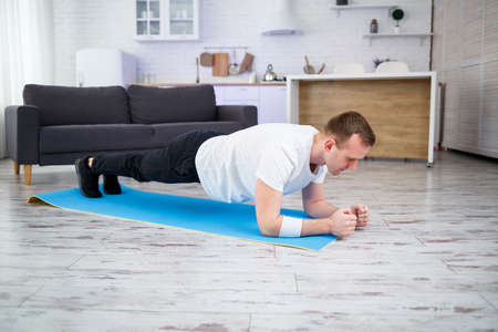 Handsome muscular man in a t-shirt doing functional plank exercises on the floor at home. Fitness at home. Healthy lifestyle. Foto de archivo