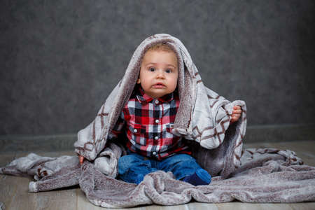 A little boy in a shirt is covered with plaid