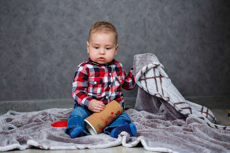 little boy ten months old in a shirt and jeans