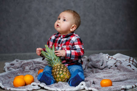The little boy in the shirt sits on the plaid and holds the fruit