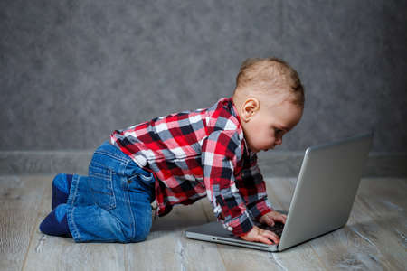 Little kid in shirt plays with laptop