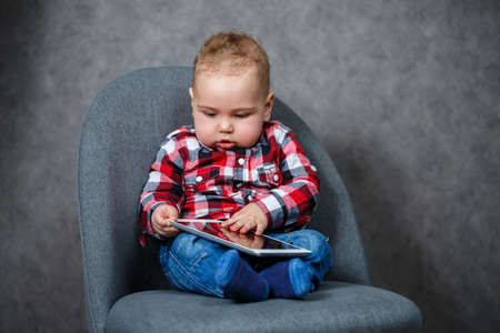 A little kid in a shirt plays with a tablet Standard-Bild