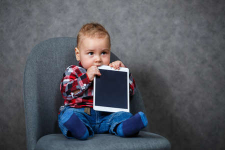 A little kid in a shirt gnaws at a tablet