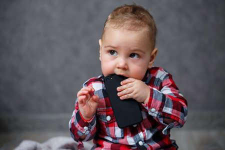 Little boy in shirt gnaws mobile phone Standard-Bild