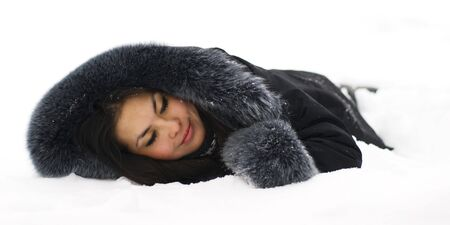 Portrait of beutiful asian young woman lying in the snow and dreaming or sleeoing. Girl isolated on white background. photo