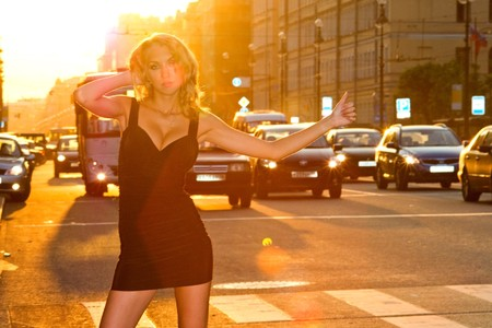 young pretty caucasian blond woman hailing a cab in the evening city. photo
